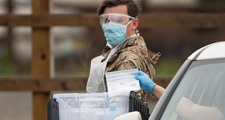 en man med munskydd med en plastlåda i famnen.