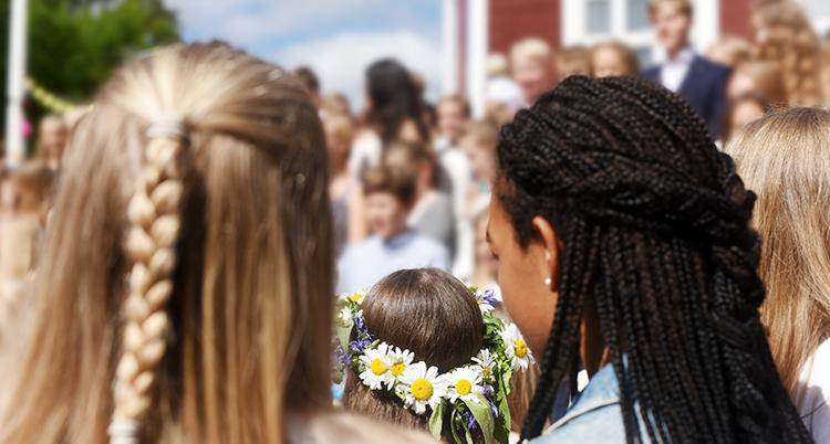 Vi ser många människor stå tillsammans, barn med kransar och flätor i håret