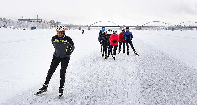 En istäckte av tunn snö. I bakgrunden är en bro. En grupp med skridskoåkare.