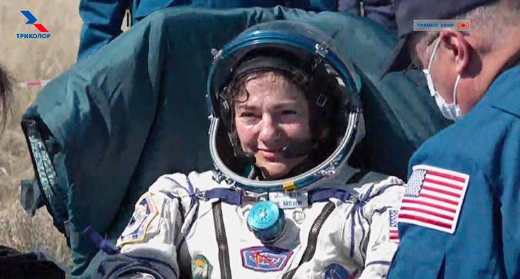 Jessica i vit rymddräkt och hjälm med öppet visir. Hon ler.