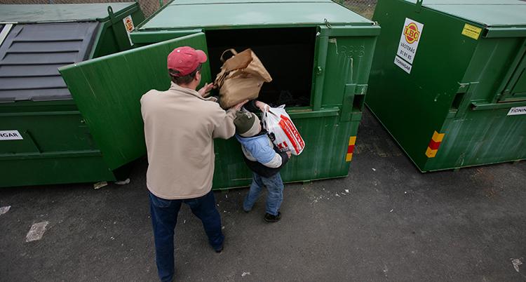 En man och ett barn slänger tidningar i en container.
