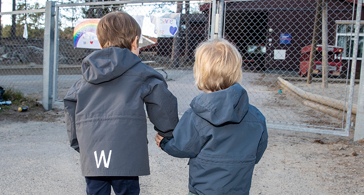 Två små barn håller varandra i handen.