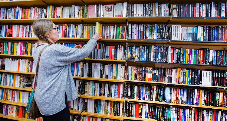 En kvinna framför en stor bokhylla