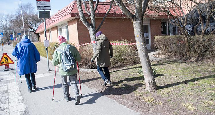 Tre äldre personer med ryggen mot kameran på vid en gata. En har stavar.