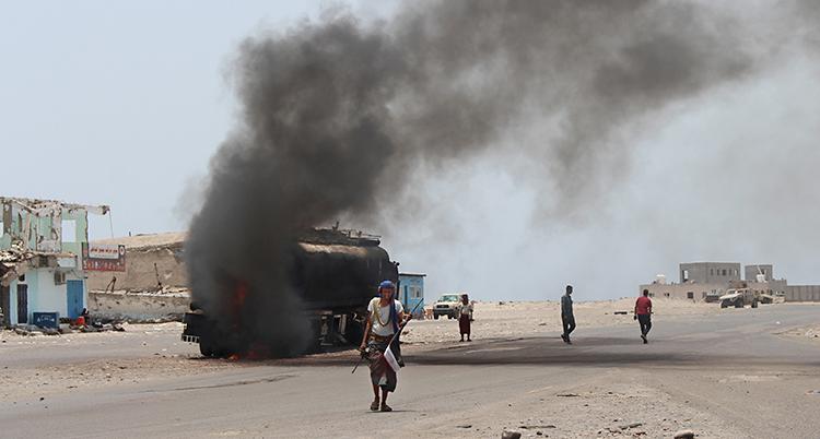 En man går framför en brinnande bil
