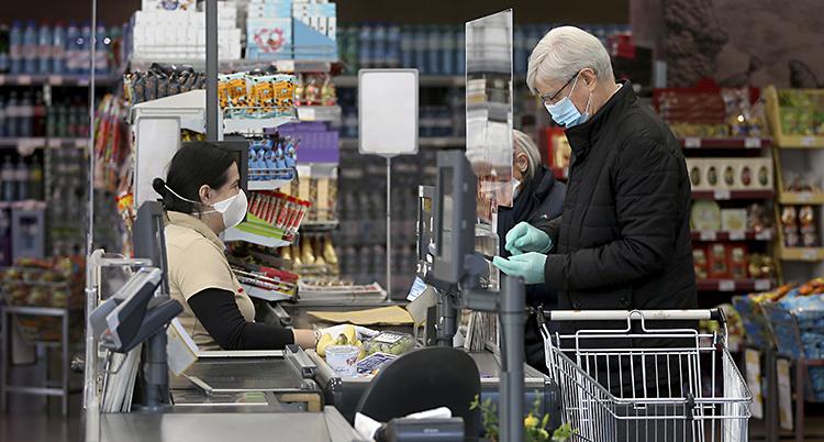 En man med munskydd och handskar betalar i en kassa i en matbutik. En kvinna med munskydd och handskar sitter i kassan.