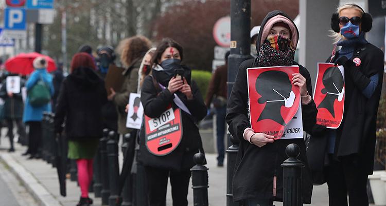 Flera kvinnor har skyltar som det står stopp på. DE har också munskydd på sig. Det beror på viruset corona.