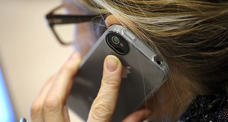En kvinna pratar i sin mobiltelefon.