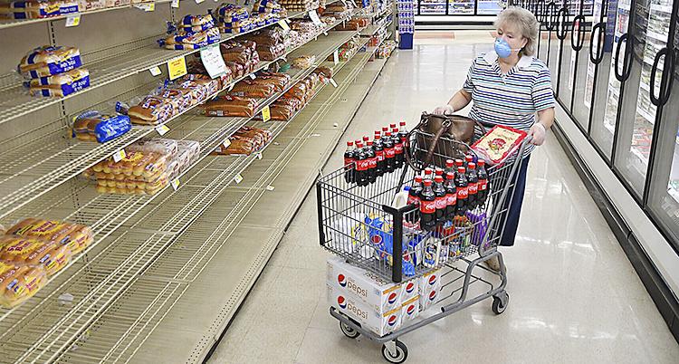 En kvinna i en affär med en vagn fylld med läsk