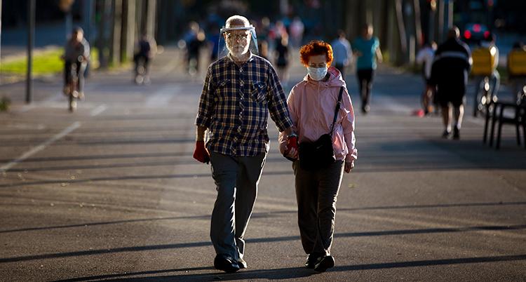 Två äldre personer på en gata. De har skydd för ansiktet