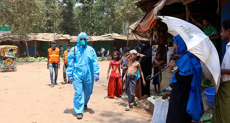En person med skyddskläder går genom lägret. Bredvid står vanliga människor och barn utan skydd