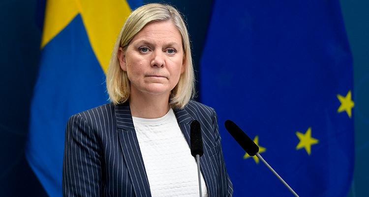 Hon ser allvarlig ut och står framför en svensk flagga. Ljust hår och svart kavaj.