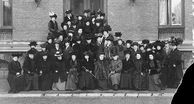Ett gammal svartvitt foto med många kvinnor samlade utanför ett hus