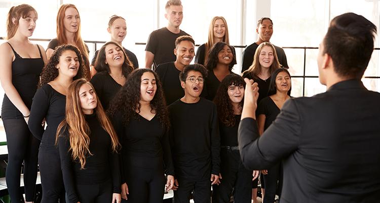 Unga människor med svarta tröjor sjunger i kör