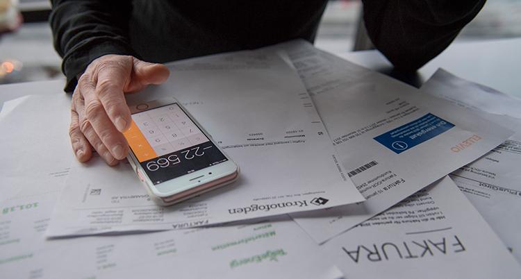 Armarna på någon som tittar på räkningar och räknar på sin mobiltelefon