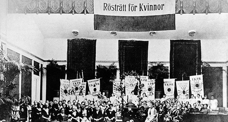En gammal svartvit bild. Kvinnorna sitter på rad under en skylt med texten Rösträtt för kvinnor