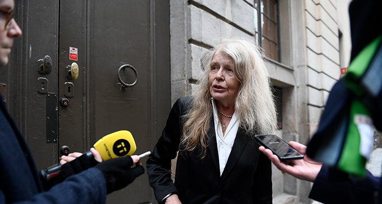 Hon har långt vitt hår och en svart kavaj. Journalister sticker fram mikrofoner