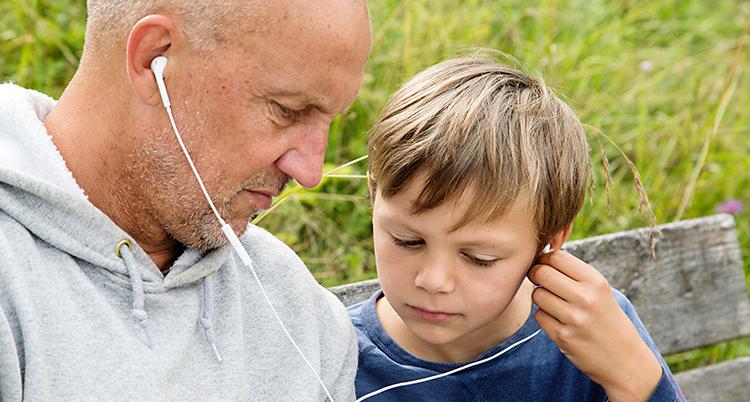 En man och ett barn lyssnar i lurar. De har varsin öronsnäcka.