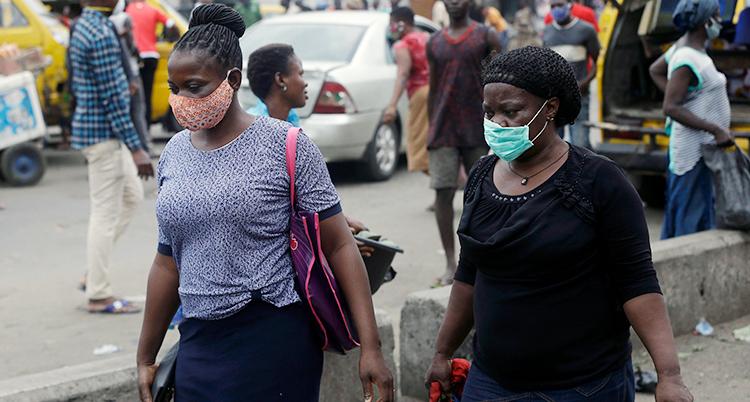 Längst fram syns två kvinnor med kassar i händerna och mask för ansiktet