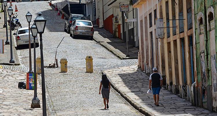 Två personer går på en gata. Där syns hus, lyktstolpar och parkerade bilar.