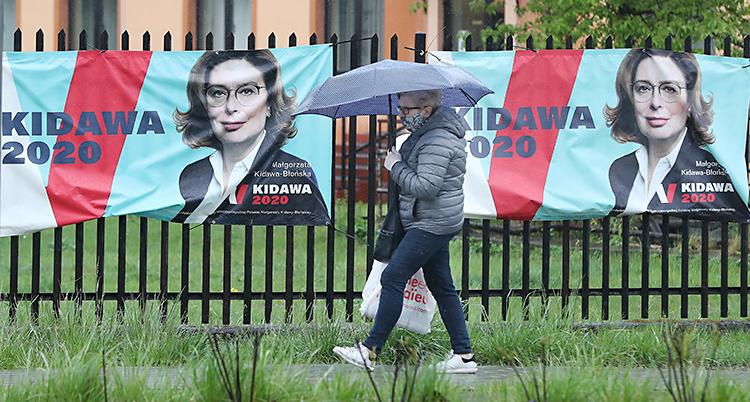 En kvinna går på en trottoar. Hon har munskydd och paraply. Bakom henne är ett staket. Där sitter affischer med en politiker på.