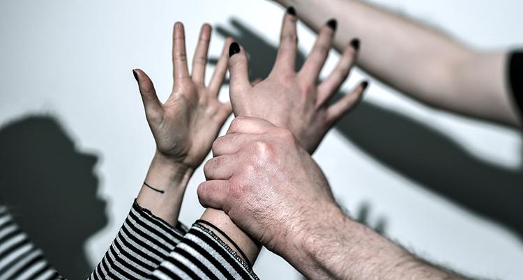 en mans hand håller fast en kvinnas hand. Hennes båda händer spärras ut. Det ser ut som att mannen ska slå kvinnan med sin andra höjda hand (som inte finns med på bild, bara en skugga)