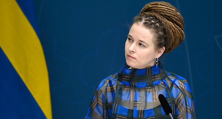 Hon har sina hår i dreadlocks i en stor knut på huvudet. Hon har en klänning som är svart och blå. Hon pratar på en träff med journalister.