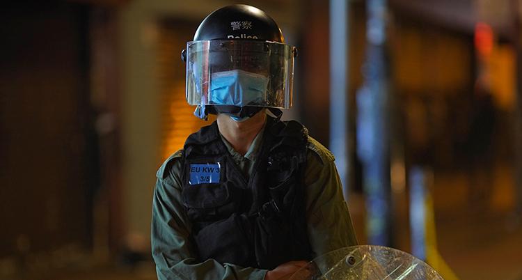 En polis med munskydd under hjälm och visir.