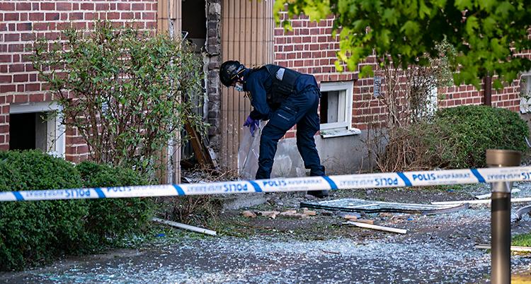 Bilden är tagen utomhus. Vi ser ett hus med lägenheter. Poliserna har spärrat av med band. Innanför bandet jobbar en polis vid porten. Porten har blivit trasig och det ligger skräp från explosionen på marken.