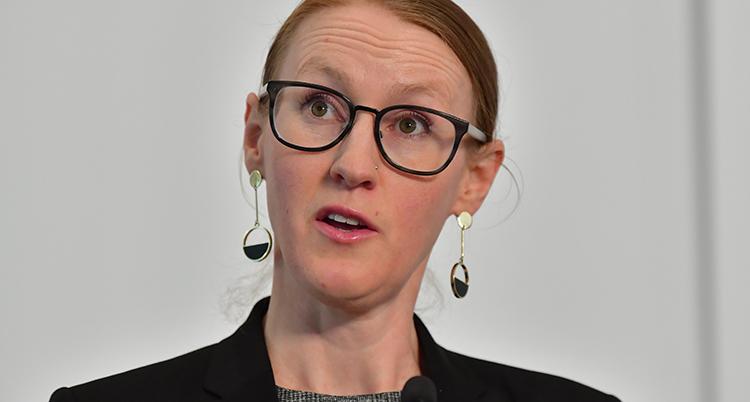 Hon har uppsatt hår, glasögon och hängande örhängen. Hon tittar snett ut ur bilden.