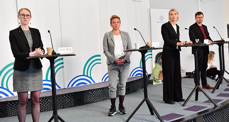 Tre kvinnor och en man står vid höga bord med mikrofoner
