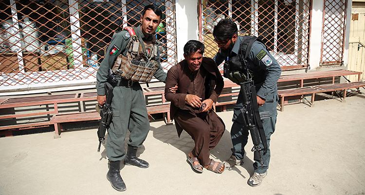 Bilden är tagen utomhus. Mannen i mitten gråter. På varsin sida står det en polis. De har vapen.