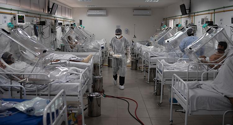 En sal på ett sjukhus med massor av sängar, patienter och olika slangar och maskiner.