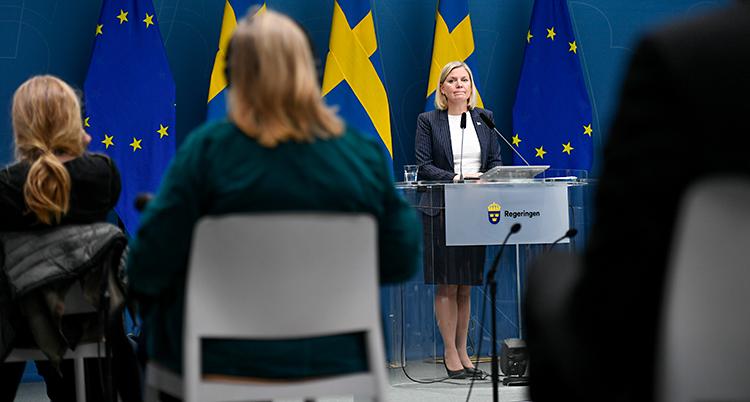 Hon står och pratar vid en talarstol. Hon pratar i en mikrofon. Bakom henne finns svenska flaggor. Framför sitter journalister på stolar.