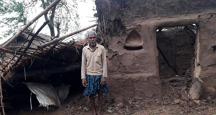 En man framför ett hus som ser ut att vara byggt av lera. Huset är skadat.
