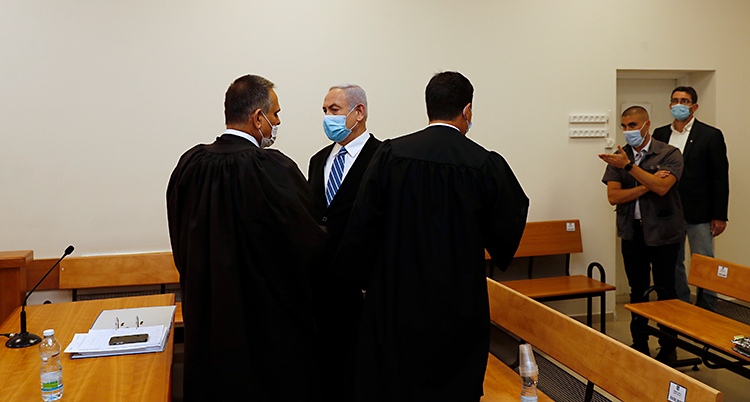 Netanyahu är i ett rum i en domstol. Han har på sig kostym. Han har också ett skydd för munnen. Det beror på viruset corona.