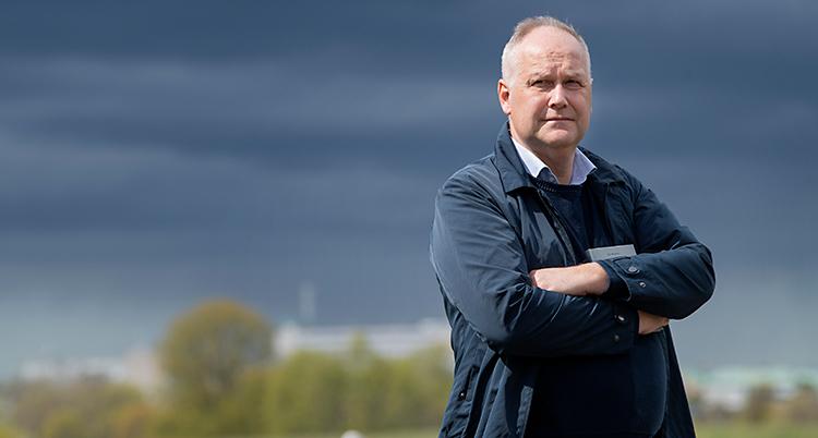 Jonas Sjöstedt står utomhus med armarna i kors. I bakgrunden är det mörka moln på himlen.