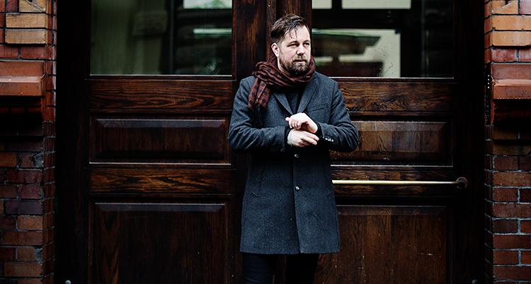 Han står utomhus. Han står framför en port till ett hus. Han har en jacka och en röd halsduk.