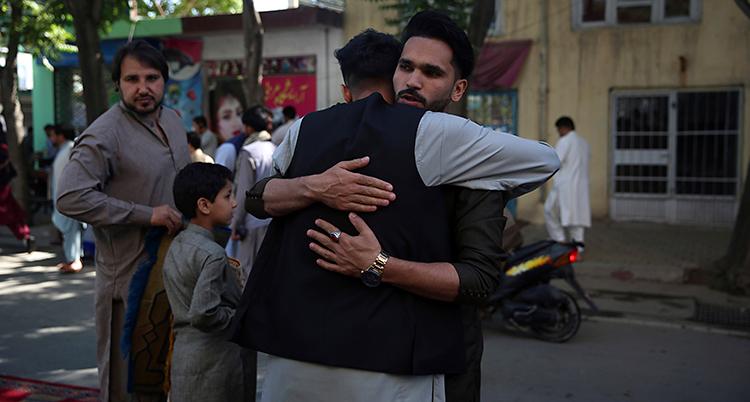 Två män kramar varandra. De står utomhus vid en gata.