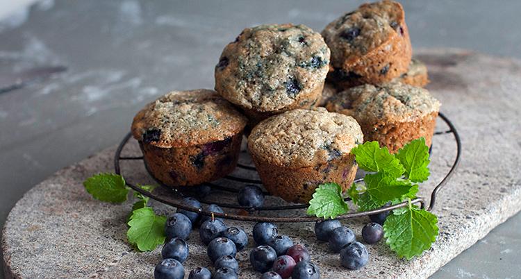 Bilden visar ett fat. På fatet ligger flera muffins. Bredvid ligger det blåbär.
