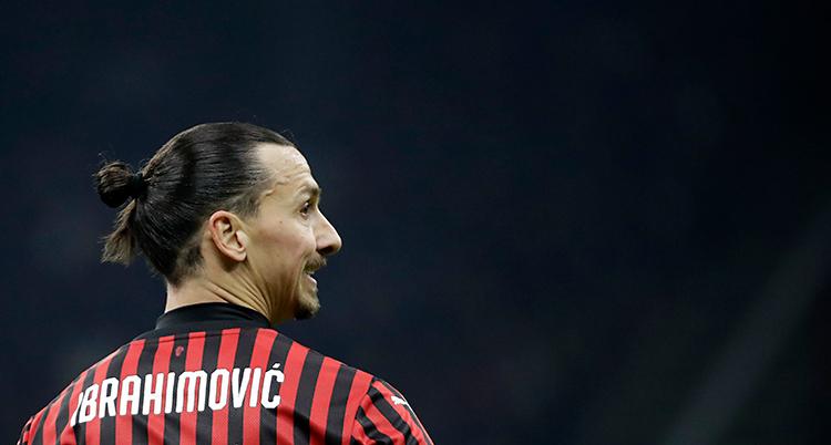 Zlatan på en match. Han har en tröja som är randig i svart och rött. Han har håret i en knut på huvudet.