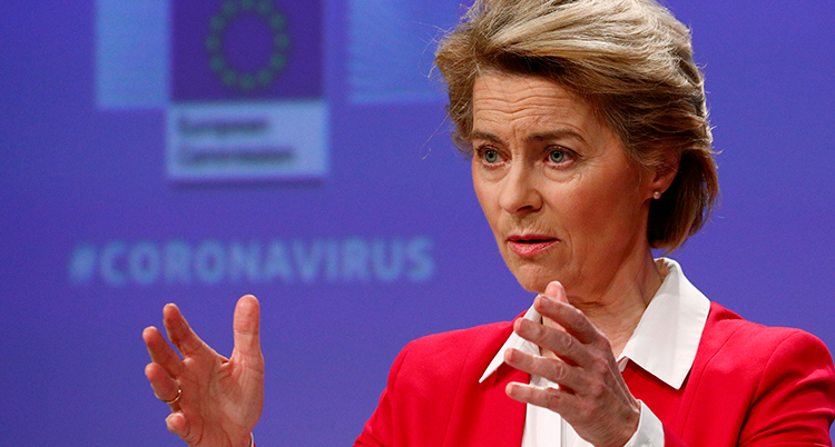 Ursula von der Leyen i röd kavaj måttar med händerna framför sig.