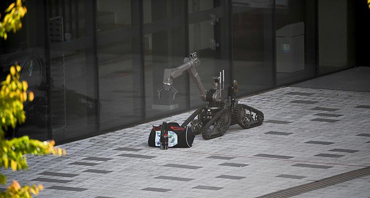 En robot är utanför ett hus. Den är nära en väska.