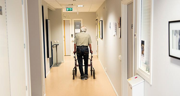 En man med rullator går i en korridor. Vi ser honom bakifrån.