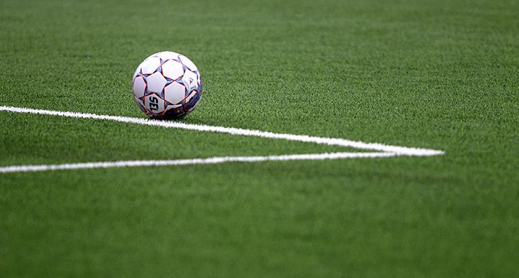 Bilden visar en fotboll som ligger på en fotbollsplan.
