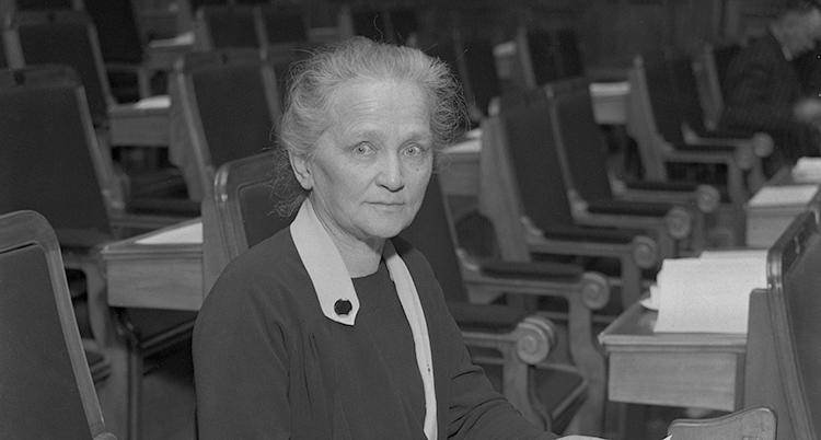 En närbild på Agda Östlund. Hon sitter i sin bänk i riksdagen.