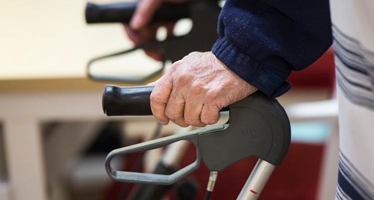 En äldre med en rollator. Vi ser händerna på handtagen.