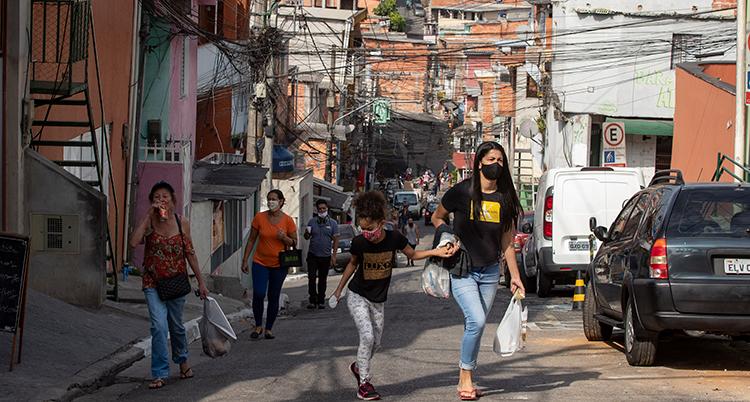 De går på en gata. De har munskydd på sig.