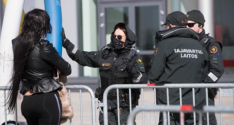 Tre finländska poliser vid ett staket. En ung kvinna står på andra sidan staketet.