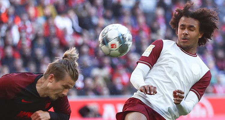En spelare nickar, den andre försöker att stoppa bollen.